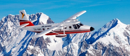 a plane flying over a snow covered mountain