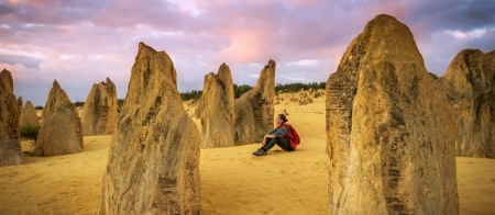 a man riding on top of a rock with Nambung National Park in the background