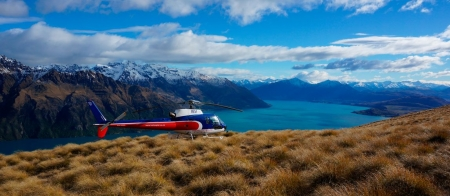 a blue and white plane sitting on top of a mountain