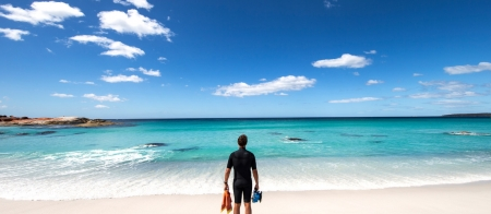 a man standing on a beach near a body of water