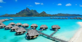 a blue umbrella next to a body of water with Bora Bora in the background