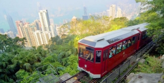 a red and white train traveling through a city