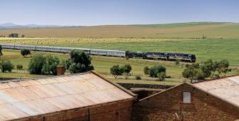 a train traveling down train tracks near a field