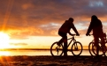a man riding a bicycle with a sunset in the background
