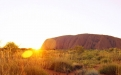 a sunset over a dry grass field with Uluru in the background