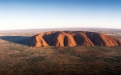 a view of a large rock with Uluru in the background