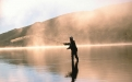 a man standing next to a body of water