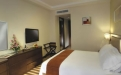 a hotel room with a bed and a flat screen tv