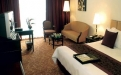 a hotel room filled with furniture and a flat screen tv
