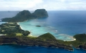 a rocky island in the middle of a body of water with Lord Howe Island in the background