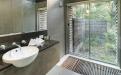 a white sink sitting under a window next to a glass shower door