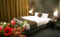 a hotel room with a bed and a vase of flowers on a table