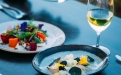 a close up of a plate of food and glasses of wine