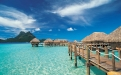 a blue umbrella sitting on top of a pier with Bora Bora in the background