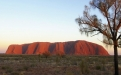 a large green field with trees in the background with Uluru in the background