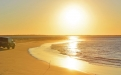 a sunset over a sandy beach next to a body of water