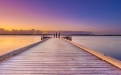a wooden pier next to a body of water