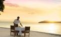 a man sitting on a beach near a body of water