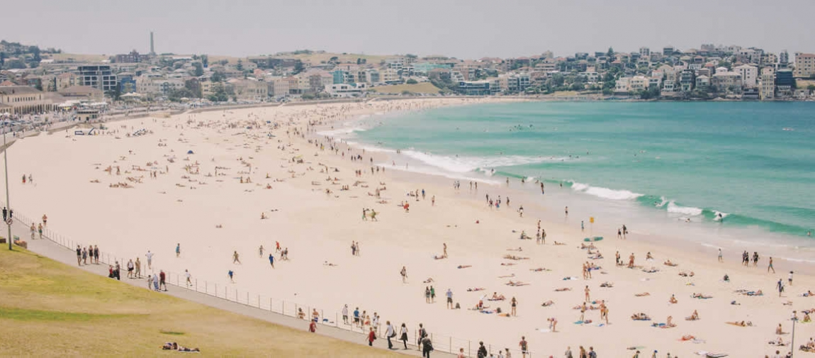 a large crowd of people at a beach with Bondi Beach in the background