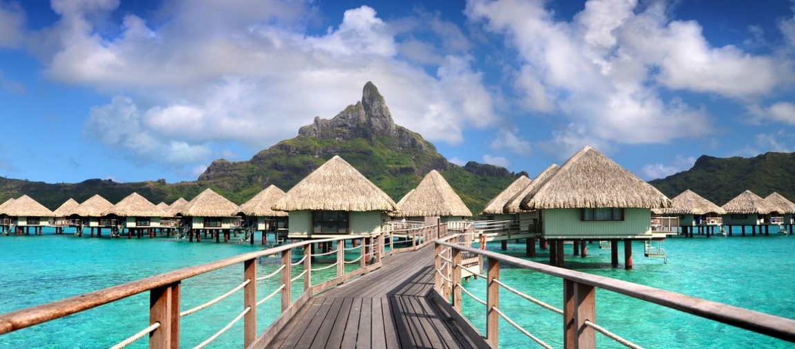 a row of wooden benches sitting next to a body of water with Bora Bora in the background