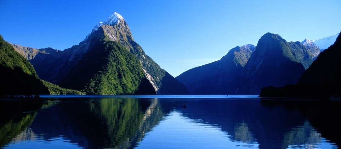 a body of water with Milford Sound in the background