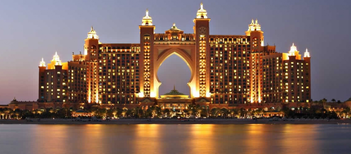 a view of a large bridge lit up at night with Atlantis, The Palm in the background
