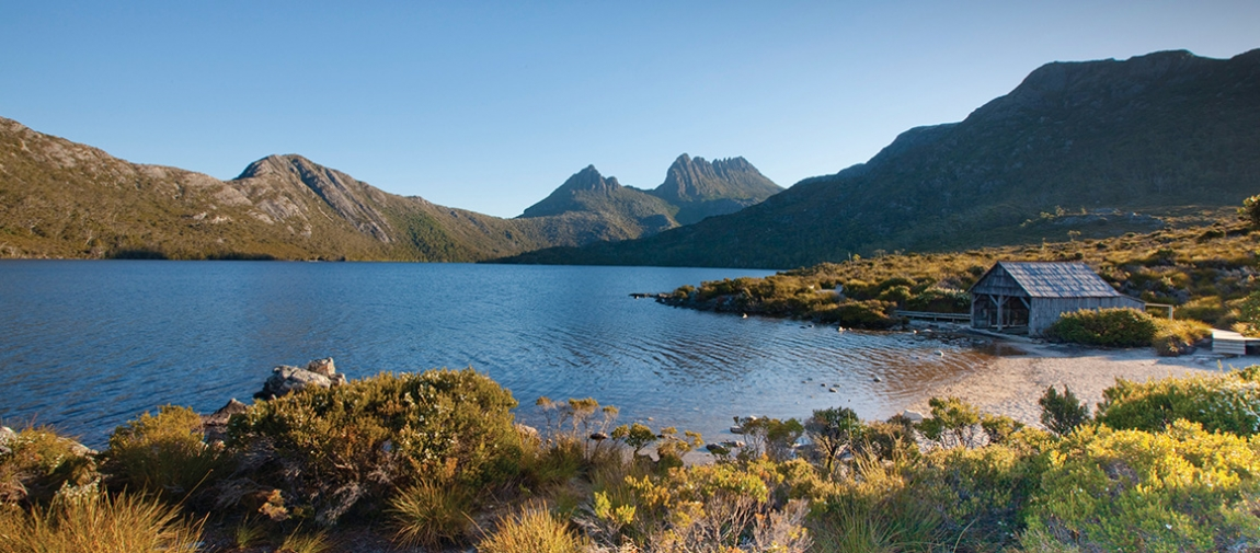 a body of water with Cradle Mountain in the background