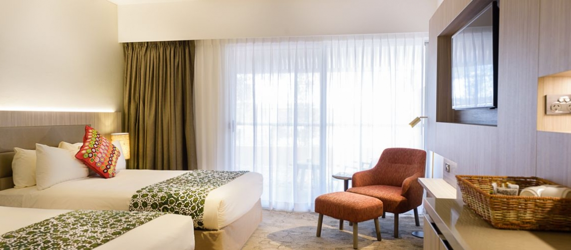 a hotel room filled with furniture and a large window