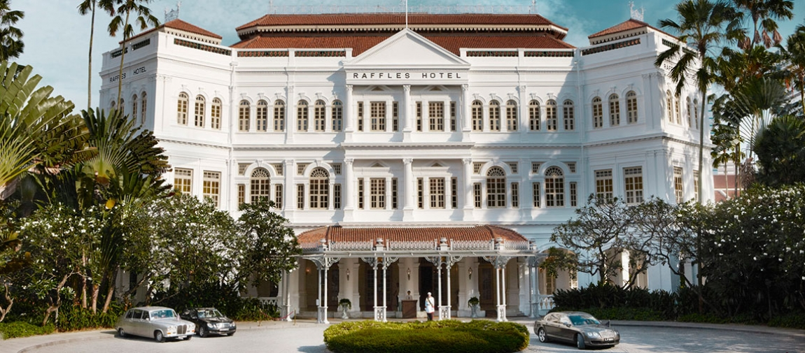 a large white building in front of a house with Raffles Hotel in the background