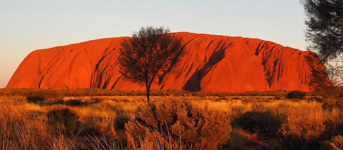 a canyon with a sunset in the background with Uluru in the background