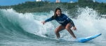 a young girl riding a wave on a surfboard in the ocean