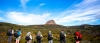 a group of people in a field with a mountain in the background